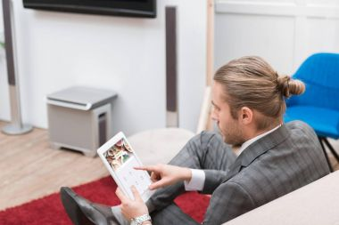 businessman using digital tablet with foursquare website at home