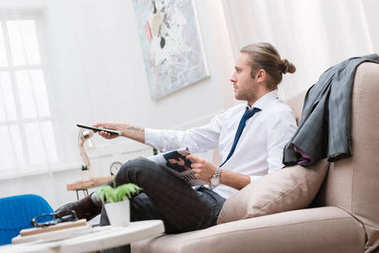 businessman with newspaper watching tv on sofa at home