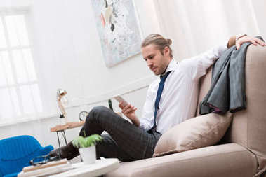 serious businessman using smartphone while sitting on sofa at home