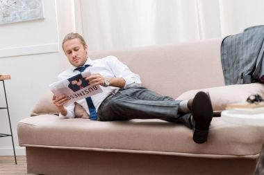 confident businessman reading newspaper while resting on sofa at home