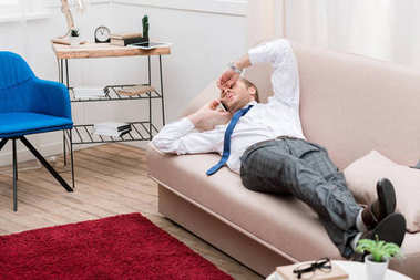 Tired businessman lying on a sofa at home and talking by smartphone