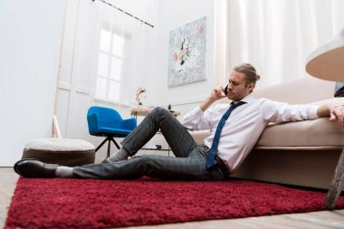 Businessman sitting on a red carpet at home and talking by smartphone