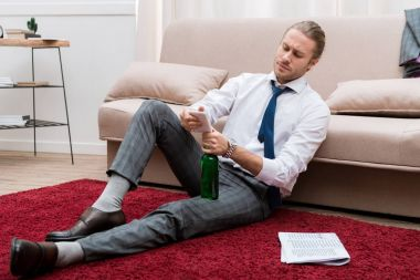 Handsome man sitting on a floor in the living room with smartphone and bottle of beer