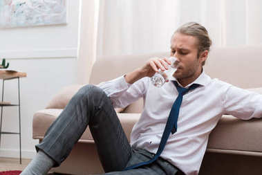 Businessman sitting on a floor at home and drinking water