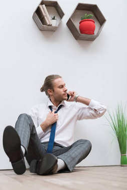 Businessman sitting on a wooden floor, talking by smartphone and loosening tie