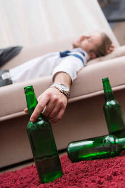 Drunk man sleeping on a sofa and holding bottle of beer