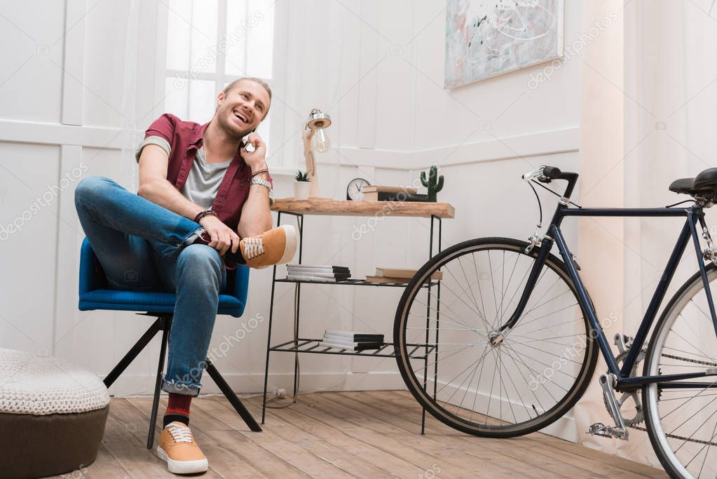 smiling man talking on smartphone while sitting on chair at home with bike