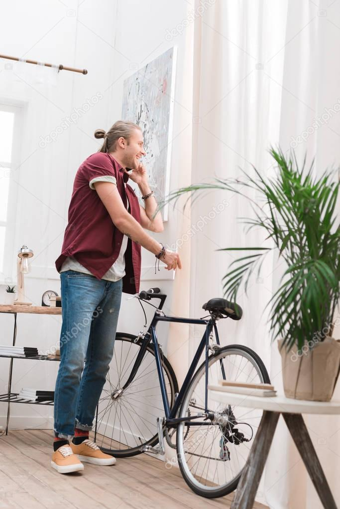 handsome cheerful man talking on smartphone and standing with bike at home