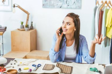 smiling designer talking by smartphone at working place
