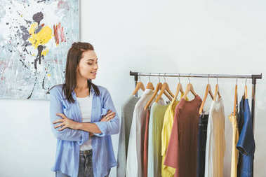smiling designer with crossed hands looking at clothes