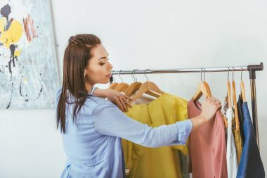 attractive designer looking at shirts on hangers