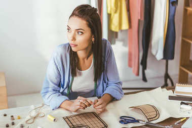 thoughtful seamstress sitting at working table and looking away