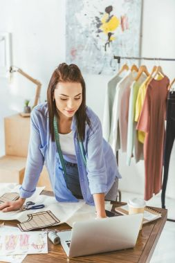seamstress standing and looking at laptop at working place