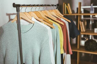different colored sweaters and shirts on hangers