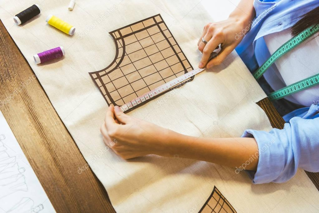 cropped image of seamstress measuring pattern at table