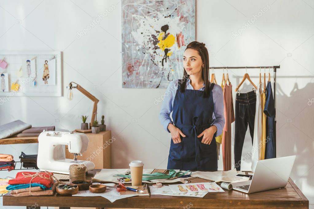young seamstress standing at working place and looking away