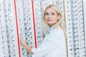 beautiful female ophthalmologist standing in optics with glasses on shelves