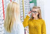 očnímu pomáhá klientovi zvolit brýle v optice