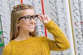 mladá usměvavá dívka výběru brýlí v optice