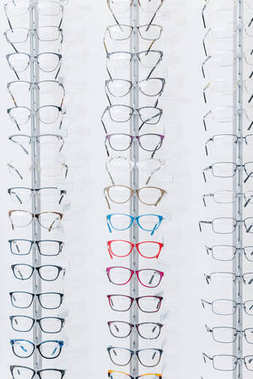 background with different eyeglasses on shelves in optics