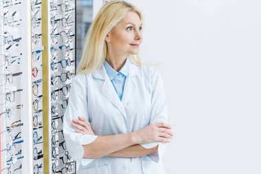 female ophthalmologist standing in optics with glasses on shelves