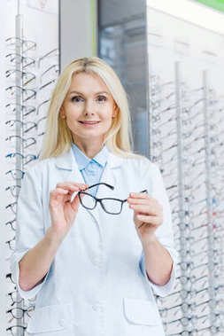 professional ophthalmologist holding eyeglasses and standing in optics