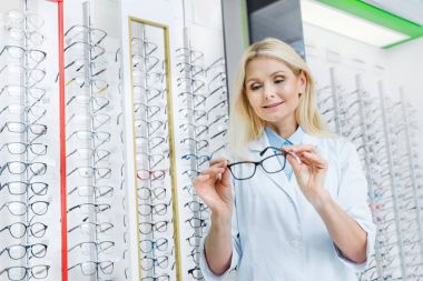 Professional female ophthalmologist holding eyeglasses and standing in optics stock vector