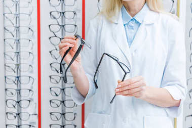 cropped view of professional female ophthalmologist standing in optics with glasses on shelves
