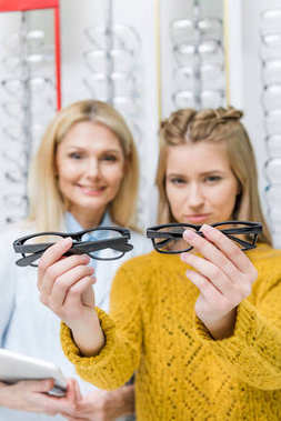 oculist helping client to choose eyeglasses in optics