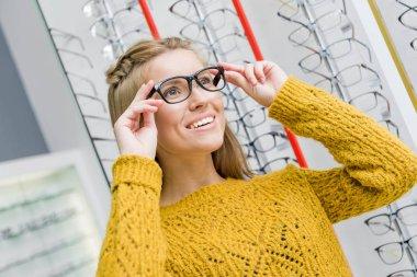 young beautiful girl choosing eyeglasses in optics