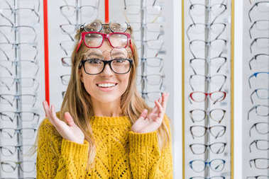 young surprised girl choosing eyeglasses in optics