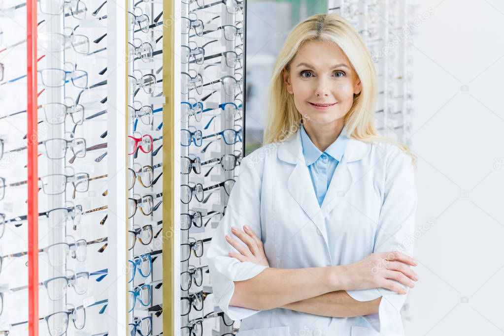 blonde female ophthalmologist standing in optics with glasses on shelves