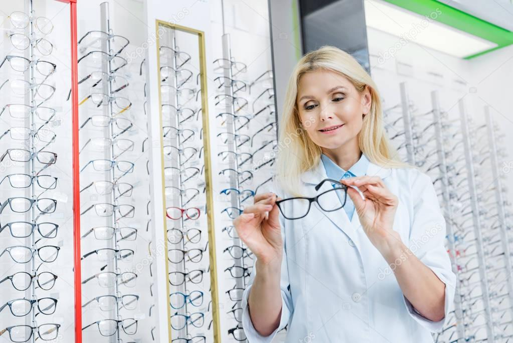 professional female ophthalmologist holding eyeglasses and standing in optics