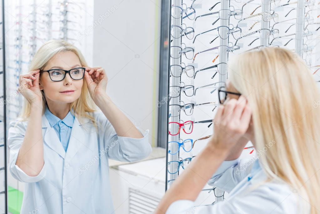 attractive female ophthalmologist wearing glasses while standing in optics