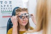 ritagliata vista Oculista e giovane paziente con prova telaio in clinica