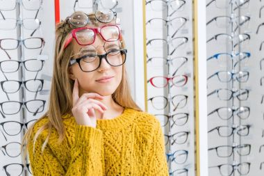 young pensive girl choosing eyeglasses in optics