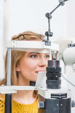 beautiful patient examining her eyes with slit lamp in clinic