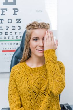 Young female patient with eye test in clinic with eye chart behind stock vector