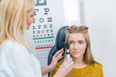 Oculist examining beautiful patient in clinic stock vector