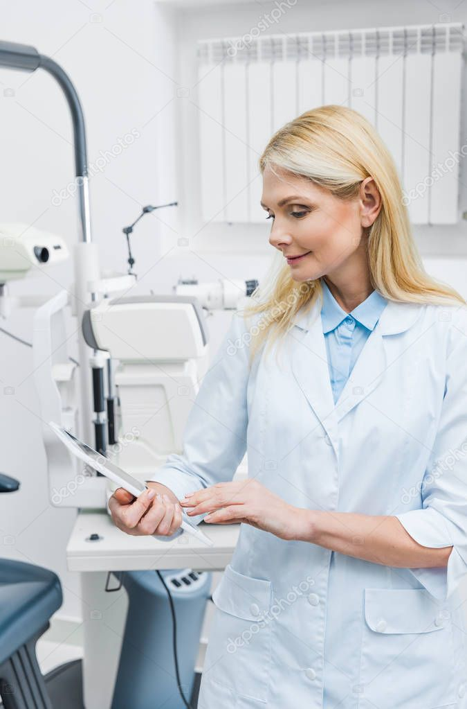 professional optician using digital tablet in clinic