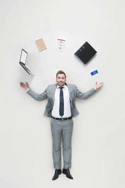 overhead view of smiling businessman with outstretched arms and office supplies above head looking at camera isolated on grey