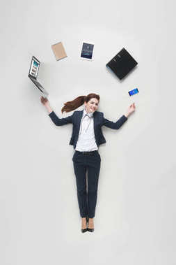 Overhead view of businesswoman with various office supplies using laptop isolated on grey stock vector