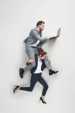 overhead view of businesswoman carrying businessman that working on laptop isolated on grey