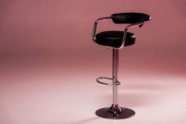 Metallic bar stool infront of pink background