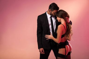 successful handsome businessman holding sexy girl in lingerie