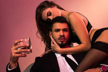 handsome businessman sitting on armchair with sexy girl in lingerie