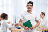 young asian student boy in classroom with friends