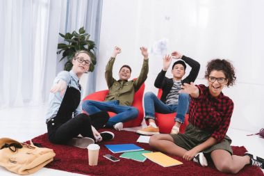 young happy students sitting and throwing paper in camera