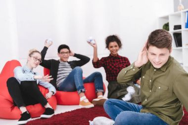 young students sitting on armchairs and throwing paper in classmate