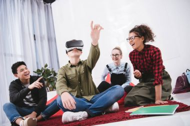 young boy in virtual reality glasses sitting on carpet with friends